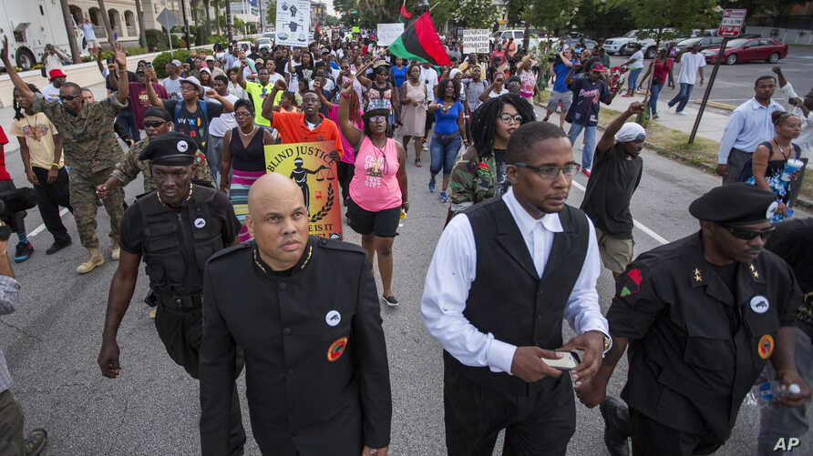 Hashim Nzinga, front left, a marcher who identified himself as national chairman of the New Black Panther Party, marches with others down Calhoun Street in Charleston, S.C., to the front of Emanuel AME Church, six days after a gunman shot nine people