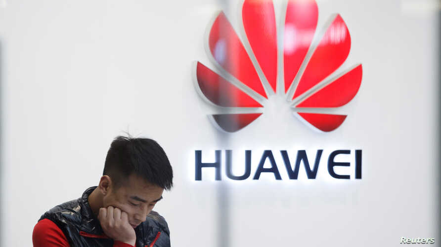 FILE - A staff member stands in front of a Huawei shop in Beijing, China, March 7, 2019.