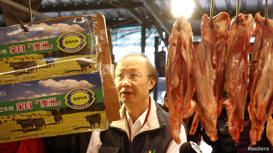 An official from the Taipei City Department of Health inspects a beef stall in a traditional market with reporters in Taipei March 22, 2012.