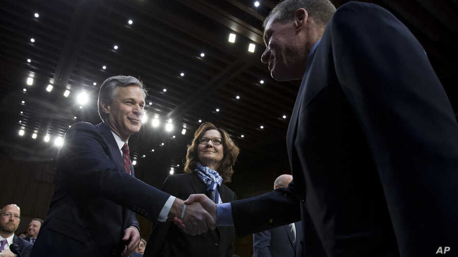 Senate Intelligence Committee Vice Chairman Mark Warner, D-Va., shake hands with FBI Director Christopher Wray as CIA Director Gina Haspel looks on before the Senate Intelligence Committee hearing on Capitol Hill in Washington, Jan. 29, 2019.