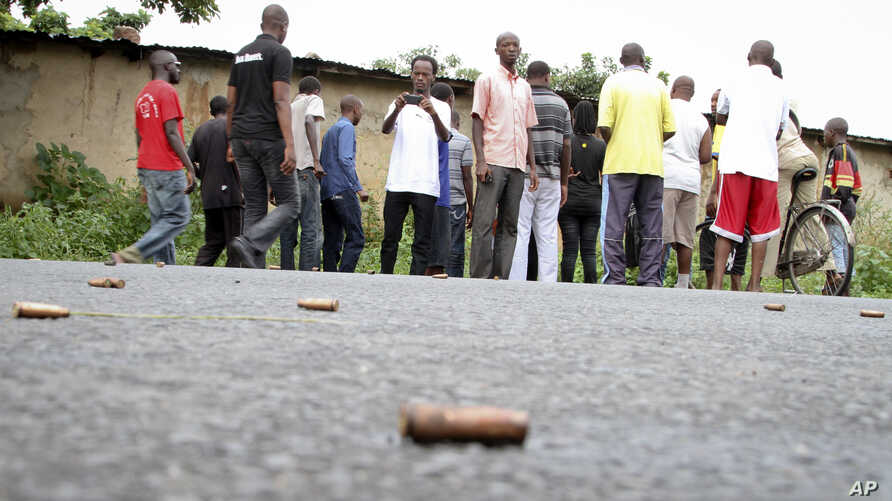 A man takes a picture of spent bullet casings lying on a street in the Nyakabiga neighborhood of Bujumbura, Burundi, Dec. 12, 2015.