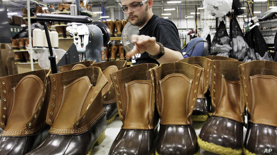 FILE - Eric Rego stitches boots in the facility where LL Bean boots are assembled in Brunswick, Maine, Dec. 14, 2011.