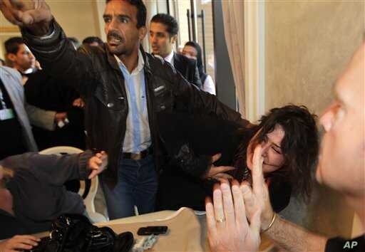A Ministry of Information official, left, yells at the press to stop filming as he  grabs Iman Al-Obeidi, who said she spent two days in detention after being arrested at a checkpoint in Tripoli, Libya,  and was sexually assaulted by up to 15 men whi