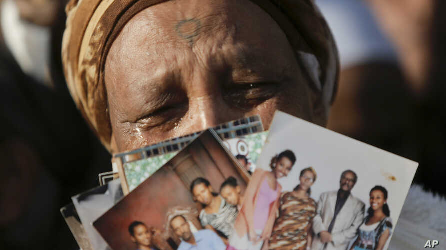 Ethiopian Israeli woman holds up pictures of relatives in Ethiopia during a demonstration in front of the Knesset, Israel's parliament, in Jerusalem, Monday, March 12, 2018. Hundreds of Ethiopian immigrants are protesting outside Israel's parliament,