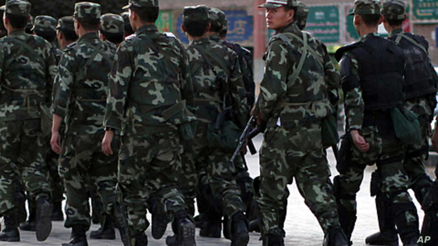 Armed police officers patrol an ethnically Uighur area in Kashgar, in Xinjiang province August 4, 2011