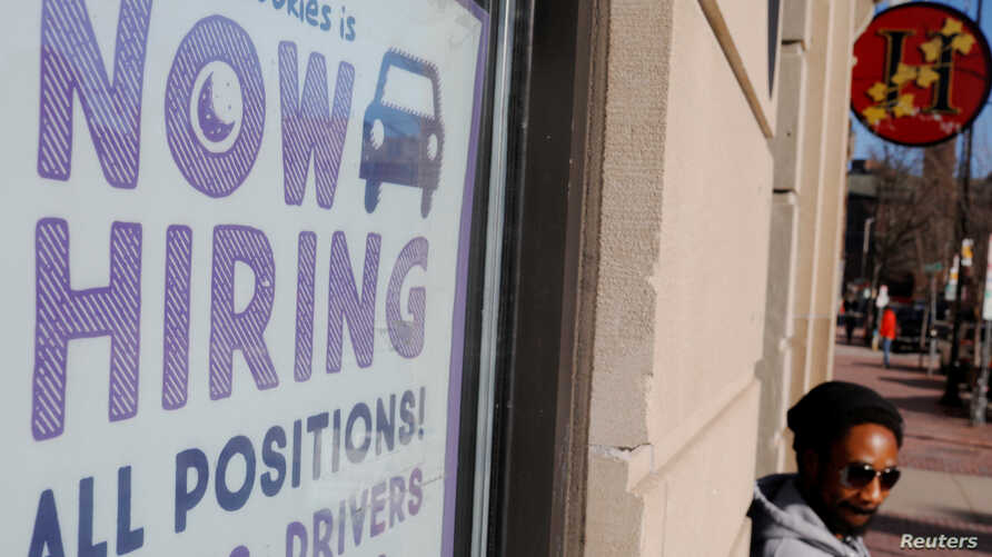 "FILE - A ""Now Hiring"" sign sits in the window of Insomnia Cookies in Cambridge, Massachusetts, Feb. 11, 2019."