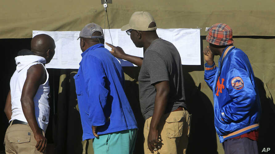 People look at results placed outside a polling station in Harare, Zimbabwe, July 31, 2018.