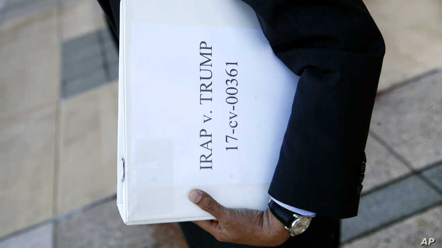 FILE - Omar Jadwat, director of the ACLU's Immigrants' Rights Project, carries court documents after a news conference outside a federal courthouse in Greenbelt, Md., Oct. 16, 2017, following a hearing regarding three lawsuits over the Trump administ