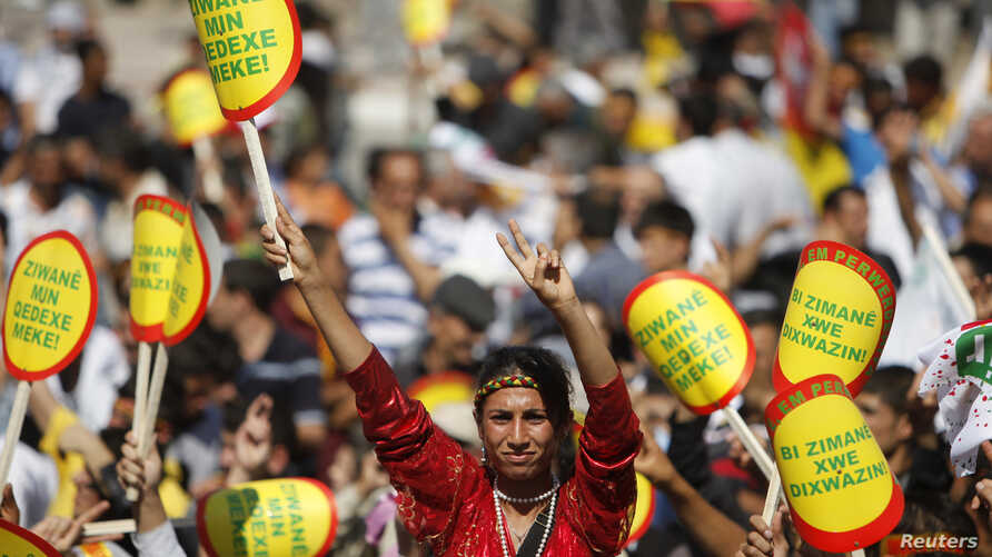 """FILE - A Kurdish woman holds a sign that reads """"Don't ban my language"""" during a rally in Diyarbakir, Turkey, Sept. 1, 2009."""