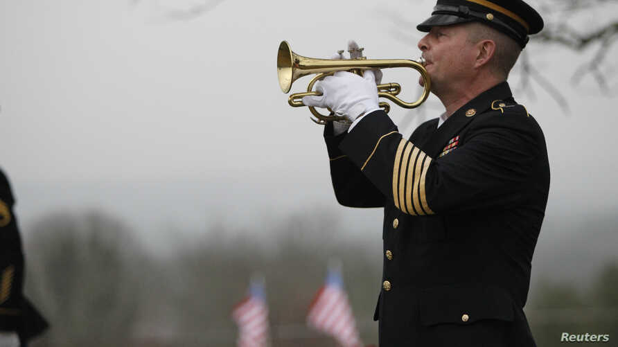 FILE - Taps is played by a lone bugler during the funeral for Korean War veteran Private First Class Glenn Schoenmann in Palmer, Tennessee, January 12, 2013.