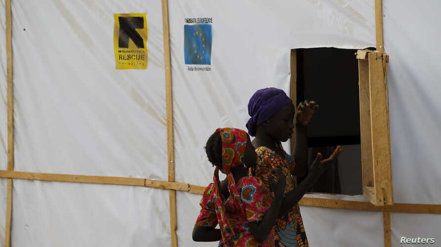 FILE - A woman and a girl are seen outside makeshift accommodations at Bakassi Camp for internally displaced people in Maiduguri, Nigeria, March 8, 2016.
