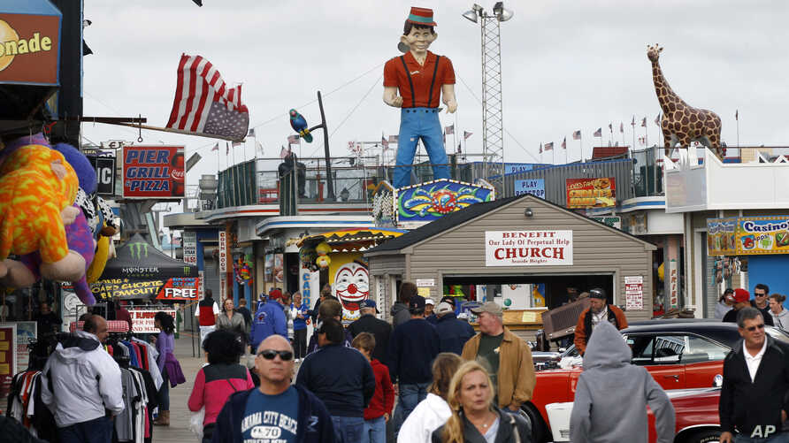 In this Oct. 13, 2013 photo, people walk along the rebuilt boardwalk in Seaside Heights, N.J.  A year ago the boardwalk was destroyed and the area was inundated by sand in the wake of Superstorm Sandy. (AP Photo/Mel Evans)