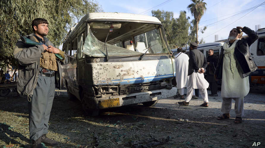An Afghan security policeman stands guard near a damaged bus after a suicide attack in Nangarhar province east of Kabul, Afghanistan, Nov. 23, 2017.