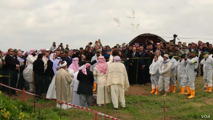 Yazidi priests release doves into the air after blessing a mass grave while the exhumation team stands by to begin their work in Kocho, Iraq, March 15, 2019.
