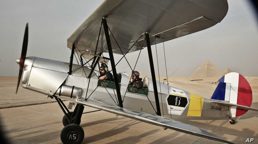 FILE - A vintage airplane lands during a rally across Africa, at the Giza Pyramids in Egypt, Nov. 13, 2016.