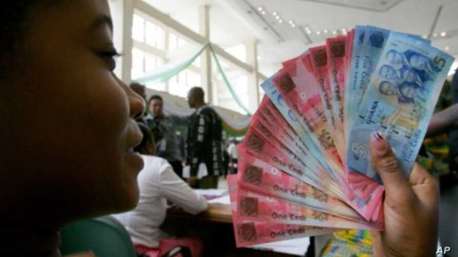A woman holds Ghana's currency (File)