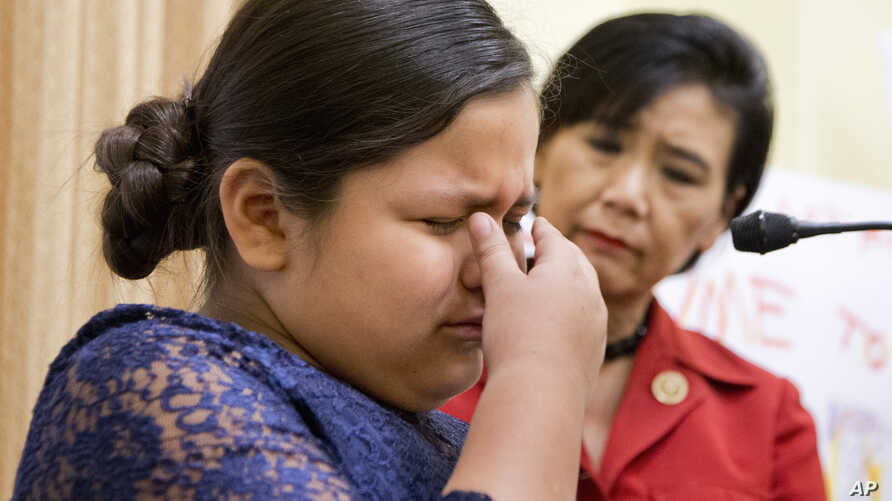 FILE -  Rep. Judy Chu, D-Calif., watches as Fiorella Zuniga from Dumfries, Va., cries during a news conference in Washington, Dec. 9, 2015. Zuniga was born in U.S. but her parents are undocumented migrants from Peru. Chu will be bringing an immigrant