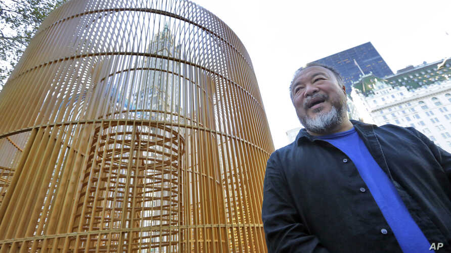 """Chinese activist artist Ai Weiwei poses by one of his """"Good Fences Make Good Neighbors"""" installations, """"Gilded Cage,"""" in New York's Central Park, Oct. 10, 2017."""