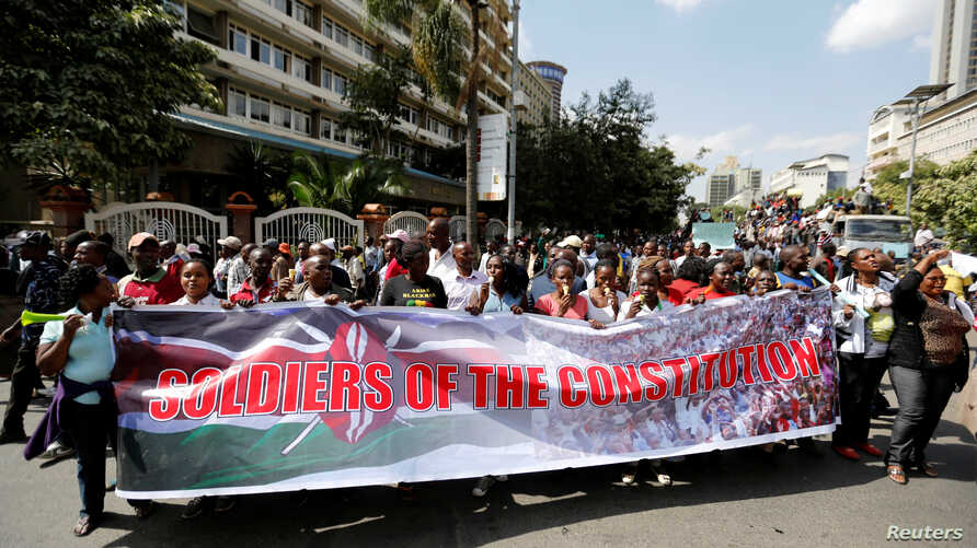 FILE - Members of Kenya's ruling Jubilee coalition carry a banner as they demonstrate in support of the Independent Electoral and Boundaries Commission (IEBC) the electoral body ahead of next year's election in Nairobi, June 8, 2016.