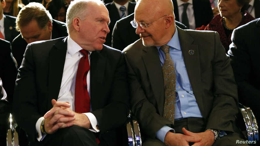 FILE - Then CIA Director John Brennan (L) speaks to then Director of National Intelligence James Clapper at the Justice Department in Washington, Jan. 17, 2014.
