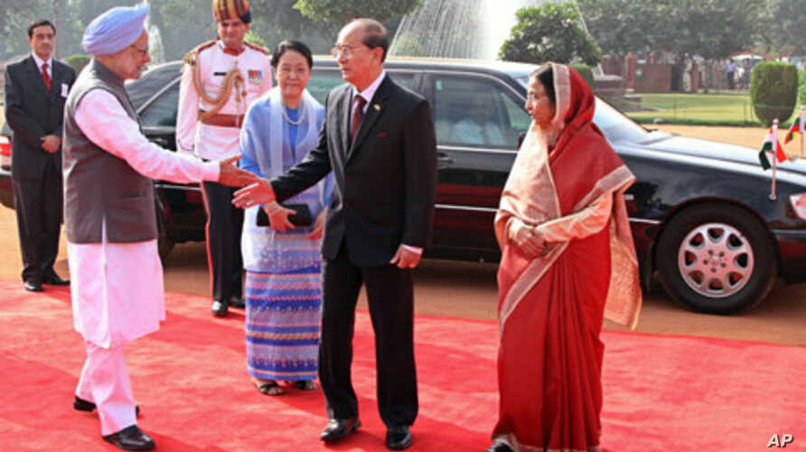 Burma's President Thein Sein (2nd R) extends his hand to Indian Prime Minister Manmohan Singh as India's President Pratibha Patil (R) and Sein's wife Khin Khin Win (in blue) watch during the ceremonial reception in New Delhi, October 14, 2011.