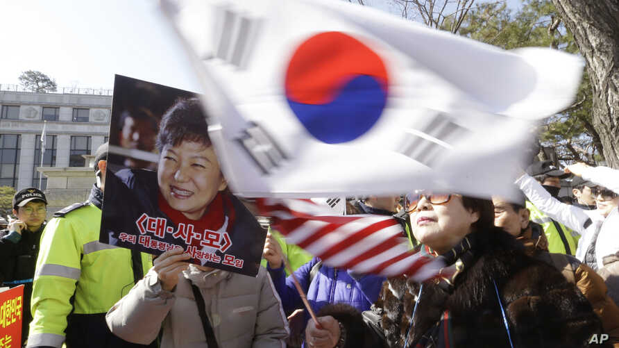 A supporter of impeached South Korean President Park Geun-hye waves flags of the U.S. and South Korea while another holds a portrait of the president during a rally in Seoul, South Korea, Feb. 27, 2017.