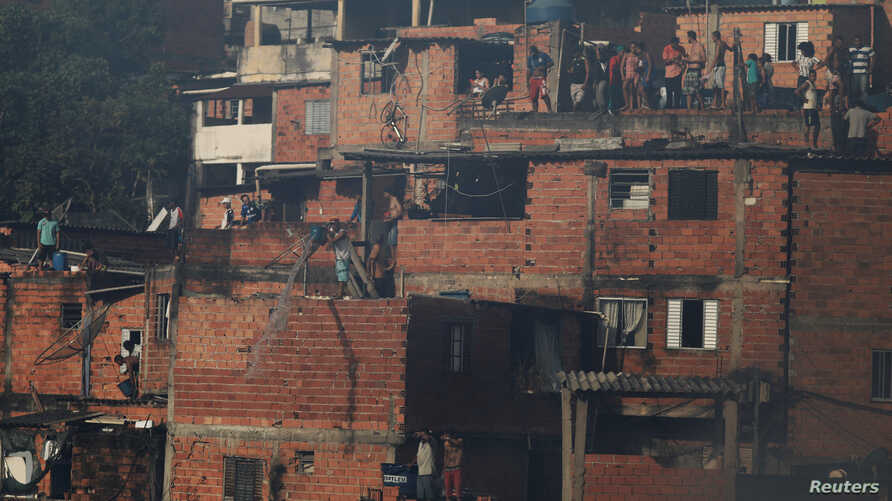 FILE - Residents pour water from their houses as they try to extinguish a fire at Paraisopolis slum in Sao Paulo, Brazil, March 1, 2017.