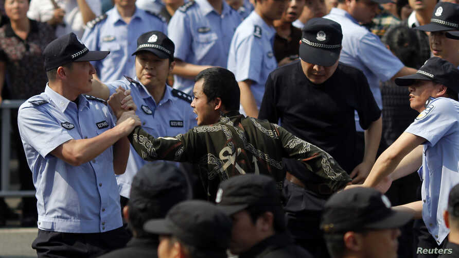 Police officers arrest a protester during a protest against plans to expand a petrochemical plant in Ningbo, Zhejiang province, China, October 27, 2012.