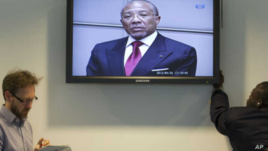 Journalists take notes as they listen to the verdict of the trial against former Liberian President Charles Taylor, seen on the screen in the court room of the Special Court for Sierra Leone in Leidschendam, near The Hague, Netherlands, April 26, 201
