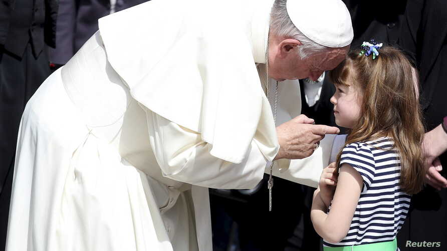 Pope Francis talks with Elizabeth 'Lizzy' Myers, a 5-year-old girl from Ohio, U.S. who suffers from a genetic disease known as Usher syndrome, which leads to blindness and hearing loss at the end of the weekly audience in Saint Peter's Square at the