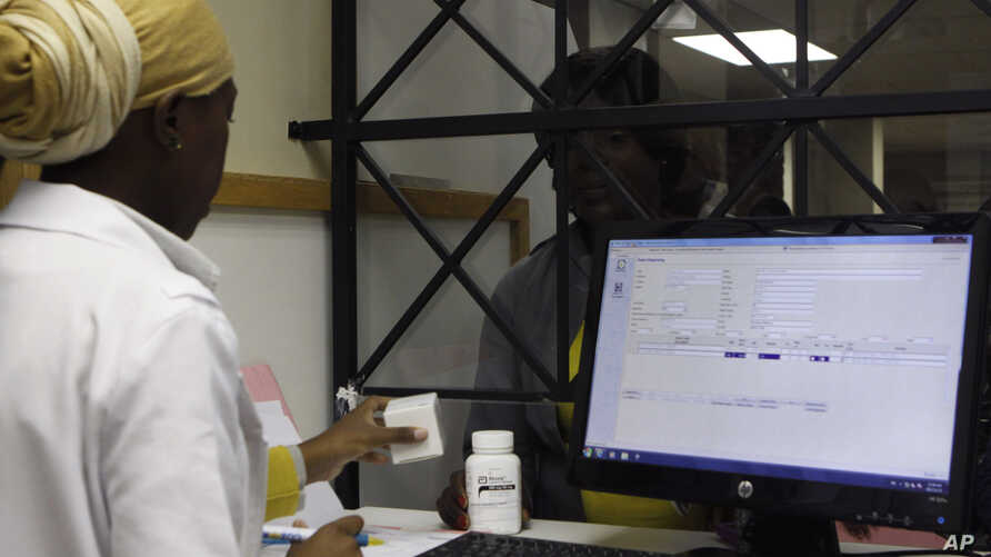 Christinah Motsoahae, back receives her medication from a pharmacist at the U.S. sponsored Themba Lethu, HIV/AIDS Clinic, at the Helen Joseph hospital, in Johannesburg, South Africa, Nov. 15, 2012.