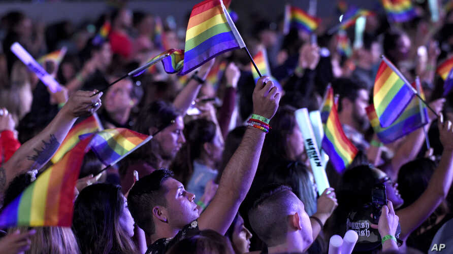 Fans waive rainbow flags in honor of LGBT Pride month in Los Angeles, June 2, 2018.