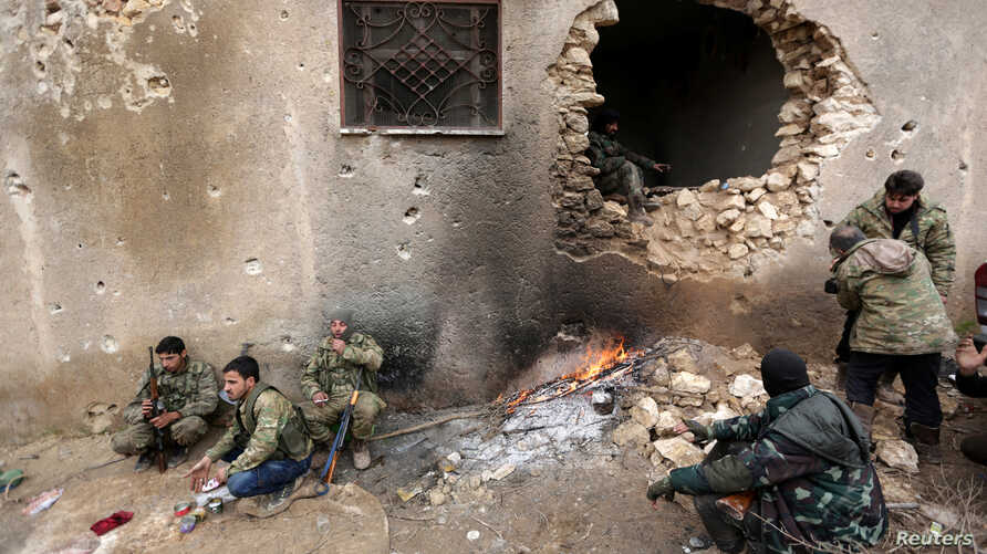 Rebel fighters rest near a hole in the wall by a fire on the outskirts of the northern Syrian town of al-Bab, Jan. 15, 2017.