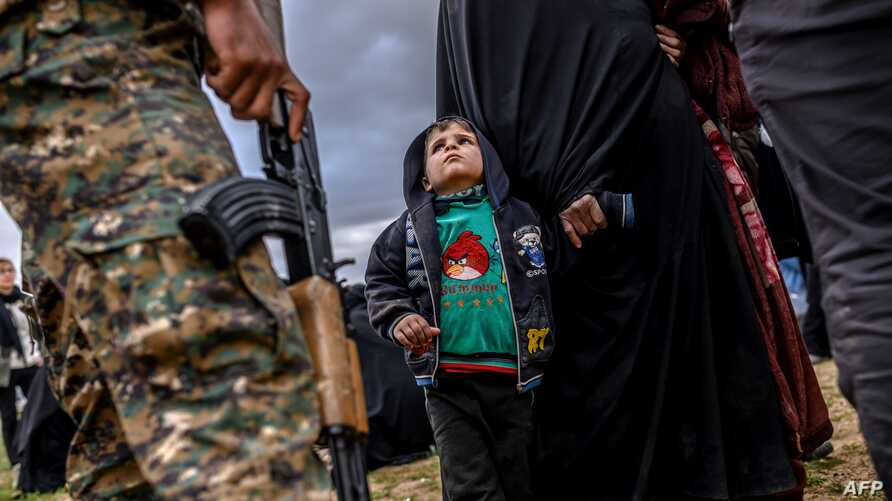 A young child looks at a member of the Kurdish-led Syrian Democratic Forces (SDF) after leaving the Islamic State (IS) group's last holdout of Baghuz, in Syria's northern Deir Ezzor province, Feb. 27, 2019.