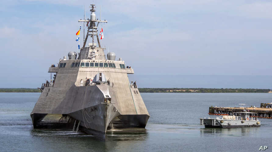 A Naval Station vessel, right, prepares to assist the future USS Omaha (LCS 12), a 218-foot-long littoral combat ship, pier side during a brief fuel stop in Guantanamo Bay, Cuba, Jan. 3, 2018. The Omaha was conducting a change of homeport to San Dieg