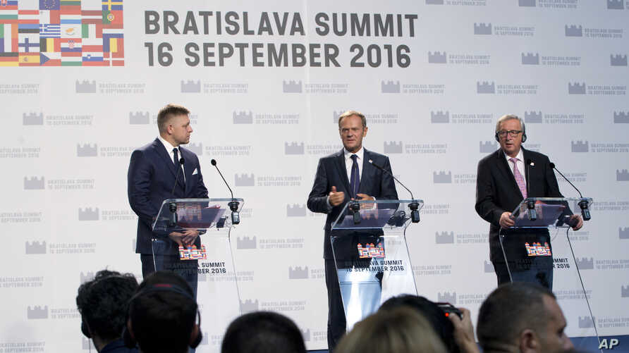 European Council President Donald Tusk, center, participates in a media conference with European Commission President Jean-Claude Juncker, right, and Slovakian Prime Minister Robert Fico at the conclusion of an EU summit in Bratislava, Sept. 16, 2016