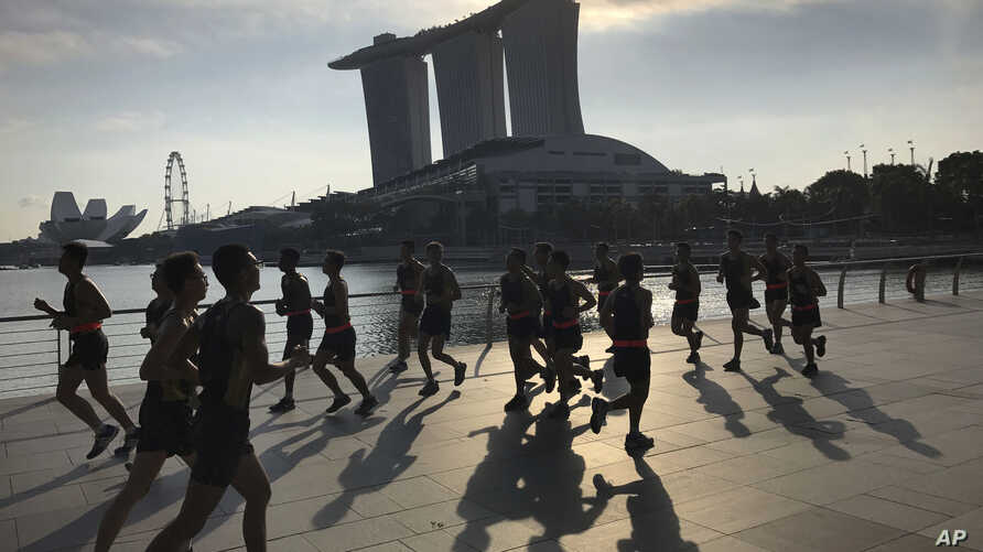 FILE - Runners pass in front of the Marina Bay Sands resort, a possible venue for the upcoming Trump-Kim summit, in Singapore.