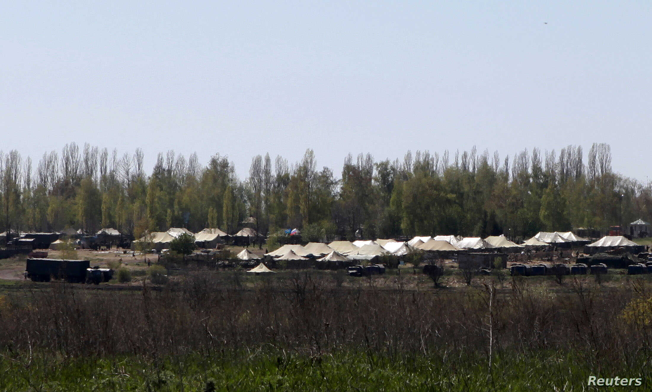 Russian military vehicles and army tents are seen in a field outside the village of Severny in Belgorod region near the Russian-Ukrainian border, April 25, 2014.