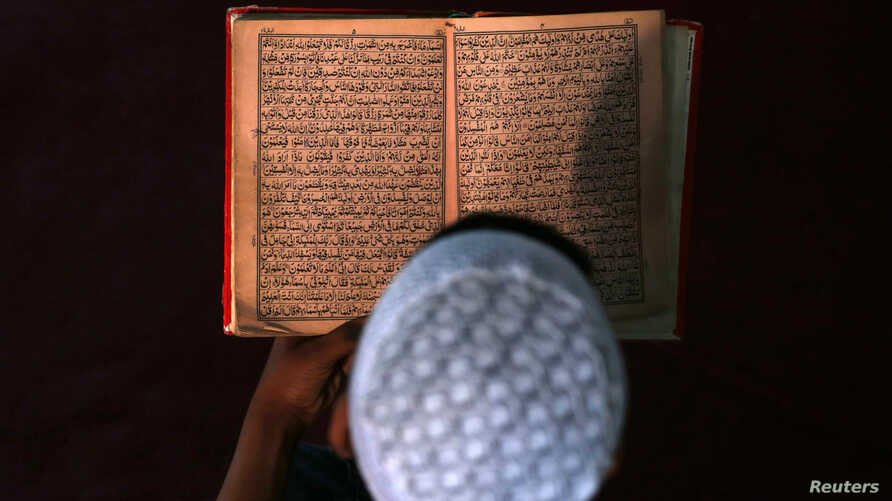 FILE - An Afghan boy reads the Quran in a madrassa or religious school in Kabul.