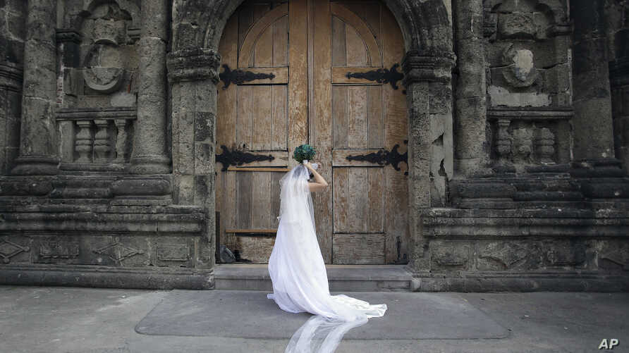 FILE - A Filipino bride arranges her gown before her wedding at a Catholic church in Manila, Philippines.