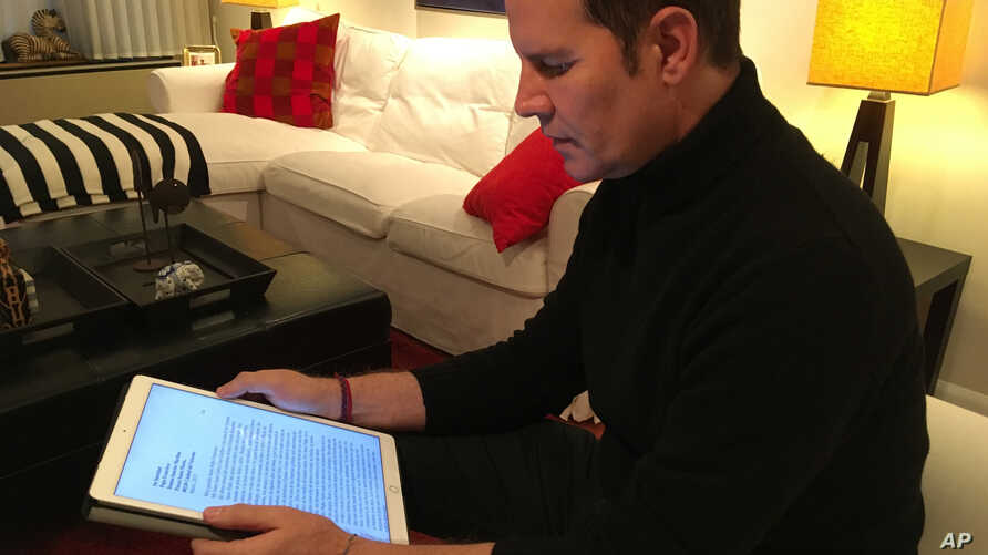 Juan Carlos Cruz reads from his tablet during an interview with The Associated Press in Philadelphia, Feb. 4, 2017.