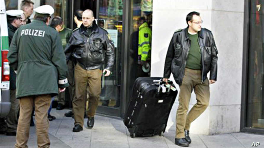 A police officer carries a suspected case out of a shop in Duisburg, western Germany, 19 Nov. 2010