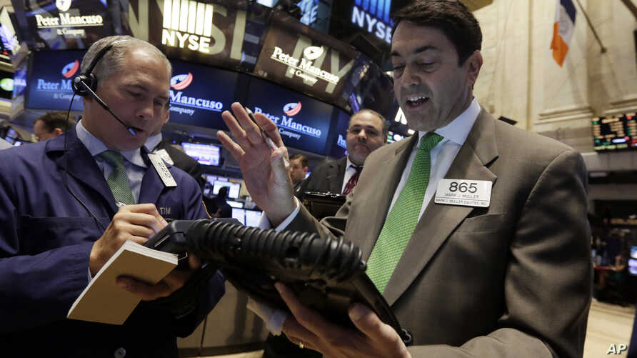 Mark Muller, right, works with fellow traders on the floor of the New York Stock Exchange, Tuesday, May 19, 2015.