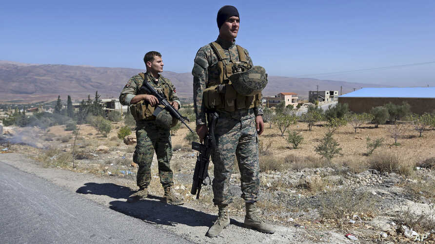 FILE - Lebanese army soldiers stand guard at an entrance to Arsal, a predominantly Sunni Muslim town near the Syrian border in eastern Lebanon, Aug. 4, 2014.