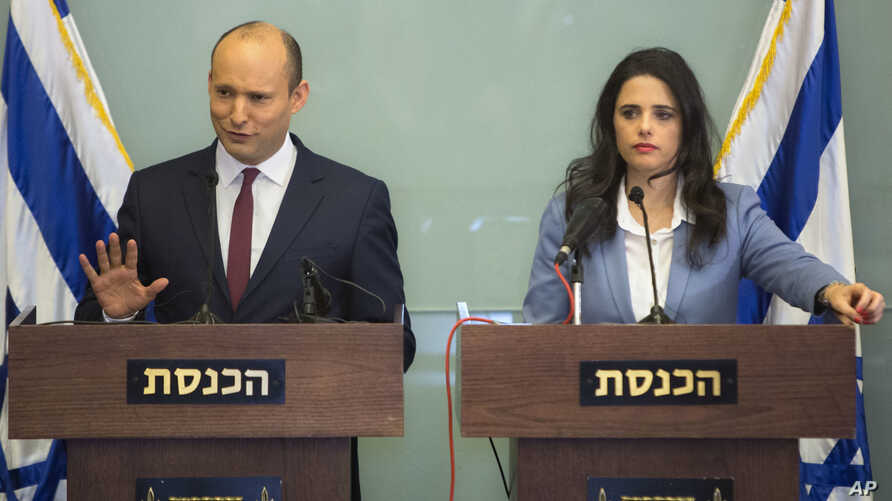 Israeli Education Minister Naftali Bennett, left, and Israeli Justice Minister Ayelet Shaked gesture as they speak during a press conference at the Knesset, Nov. 19, 2018.