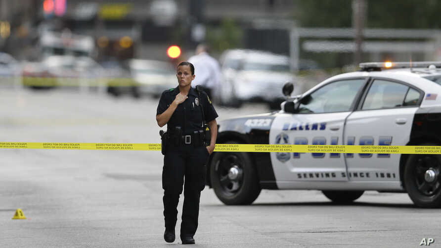 A Dallas police officer guards the scene of last night's shooting as investigators work in downtown Dallas on July 8, 2016. (AP)