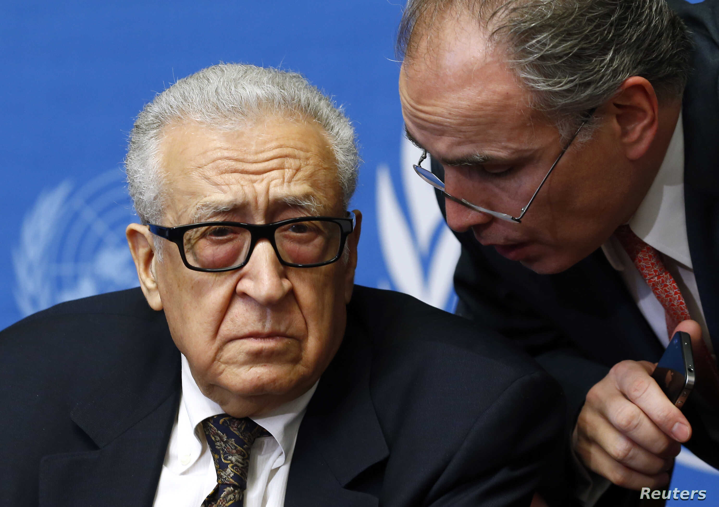 U.N.-Arab League envoy for Syria Lakhdar Brahimi (L) listens to his adviser Moncef Khane before a news conference at the United Nations European headquarters in Geneva, Feb. 11, 2014.