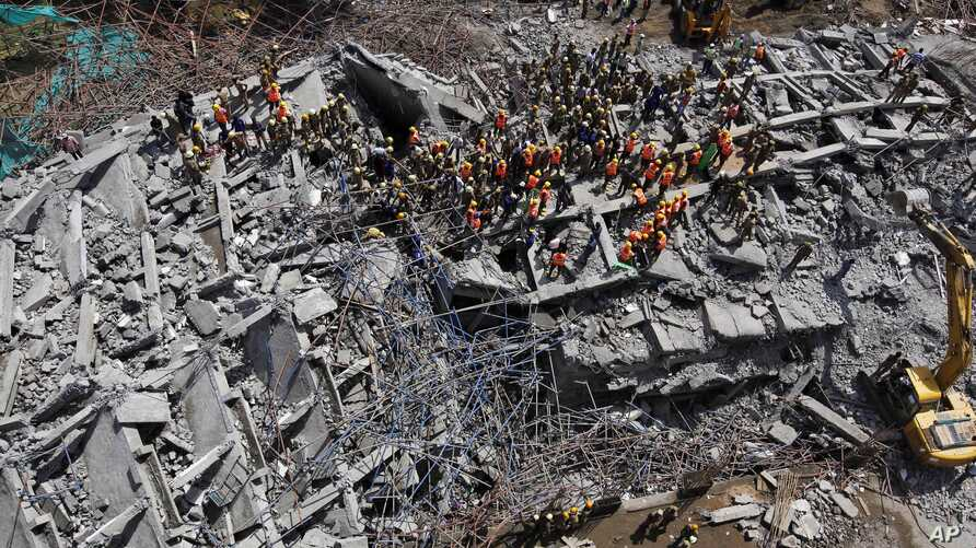 Rescuers search for workers believed to be buried in the rubble of a building that collapsed late Saturday during monsoon rains on the outskirts of Chennai, India, June 29, 2014.