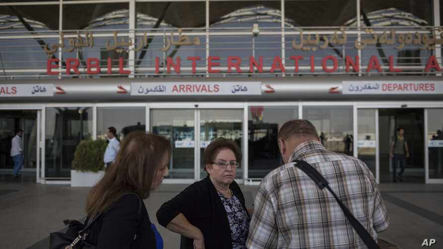 FILE - Travelers wait outside the Irbil International Airport in Iraq, Sept. 29, 2017.