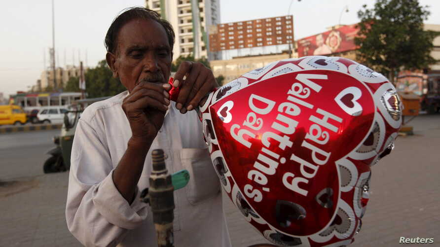 A vendor inflates a heart-shaped balloon from his cart ahead of Valentine's Day along a road in Karachi, Pakistan in this picture taken Feb. 10, 2016.